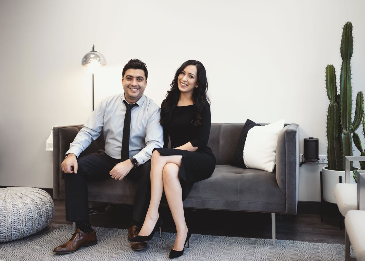 Photo of Dr. Sushant and Dr. Ritu smiling sitting on a couch in the greeting area