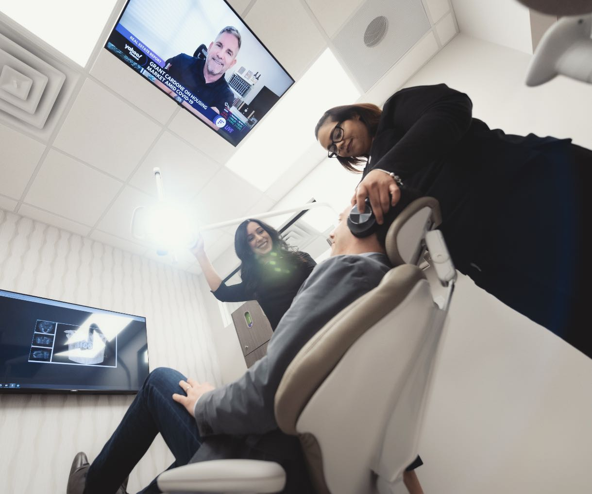 Photo of a patient getting comfortable in the operatory with headphones and watching television