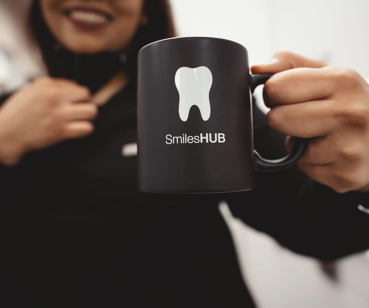 Photo of a SmilesHUB team member holding a SmilesHUB branded mug