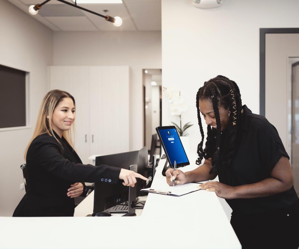 Photo of a SmilesHUB team member with a patient at the front desk