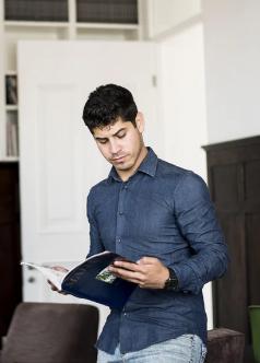 A man holding an open notebook.