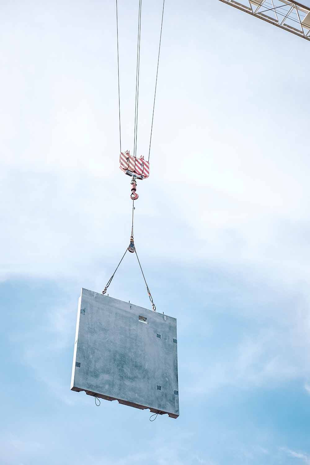 A precast concrete wall is hoisted up into the air by a crane.