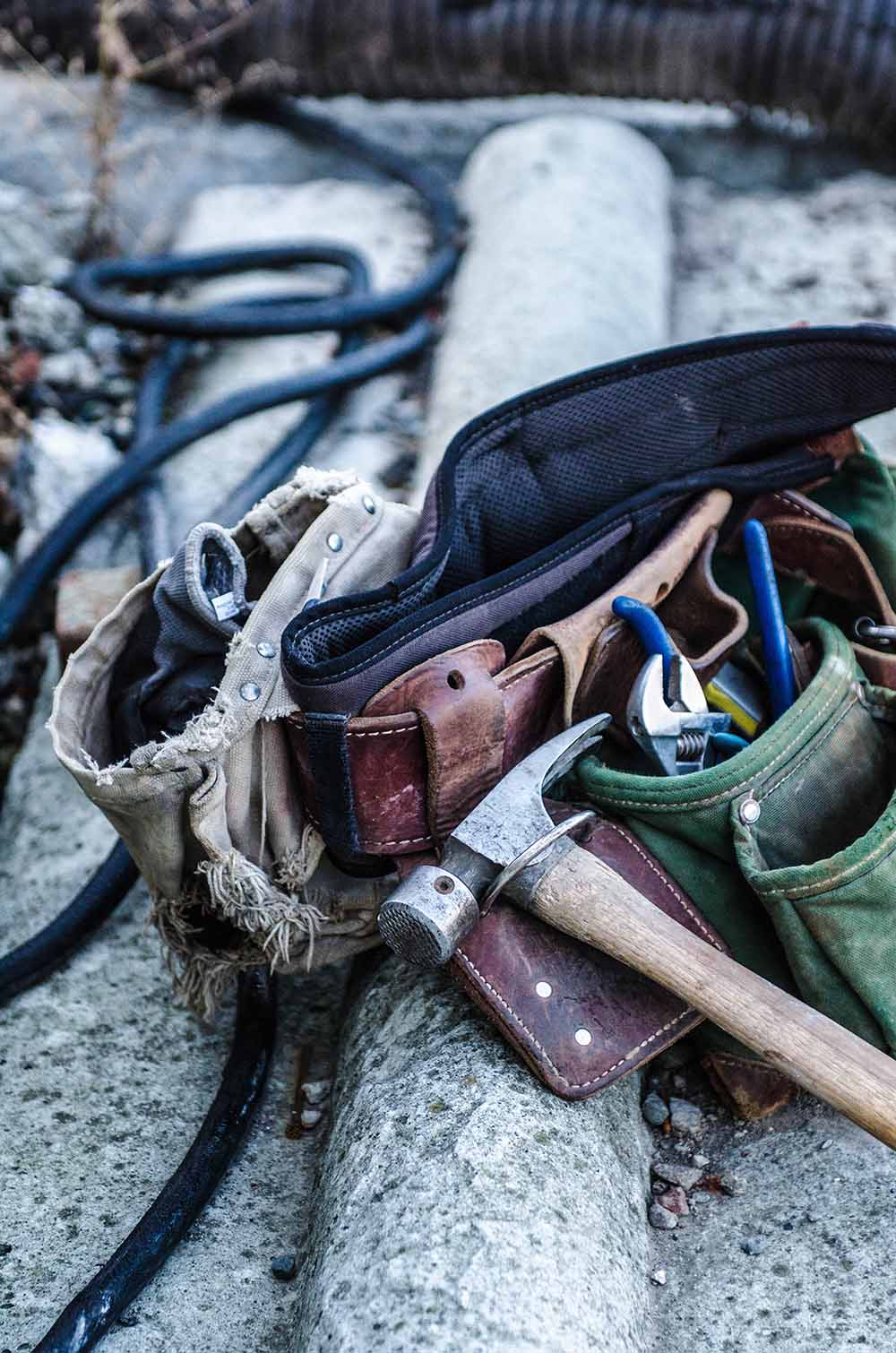 A tool belt full of tools rests on the ground.