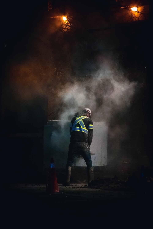 A construction worker facing a concrete culvert.