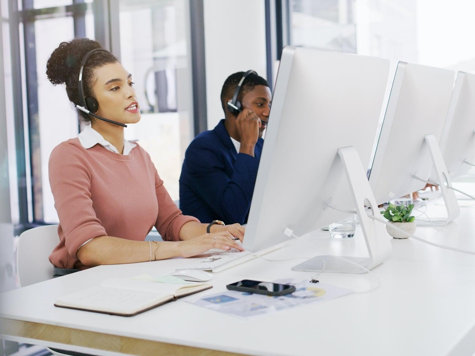 People sitting at desk answering customer calls