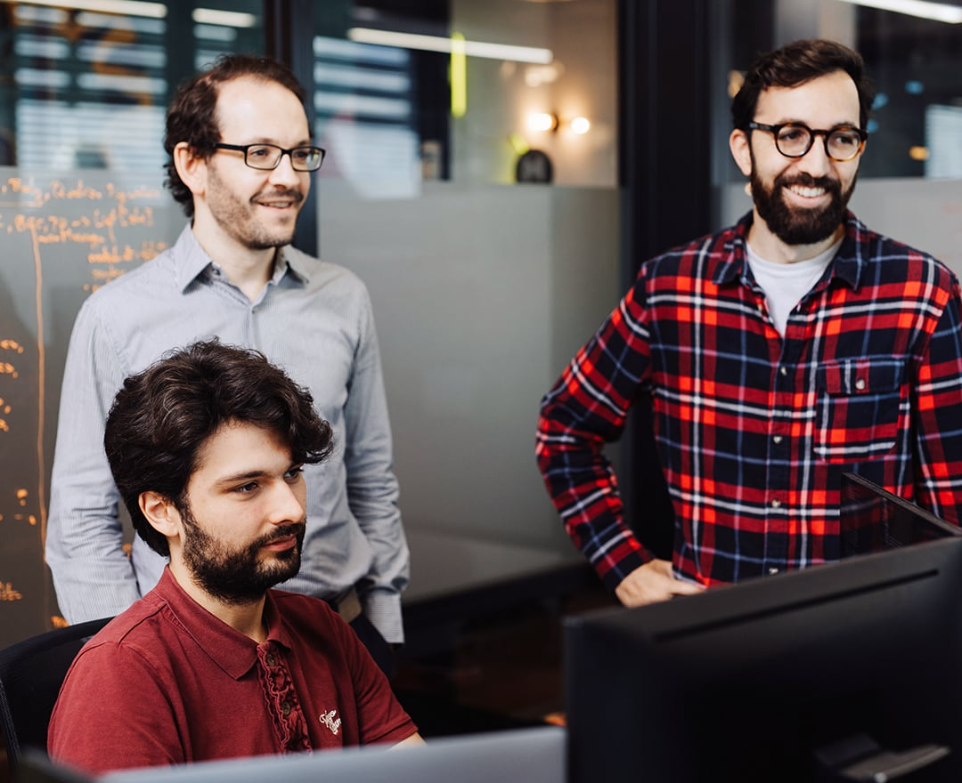 Colleagues looking at screen in office