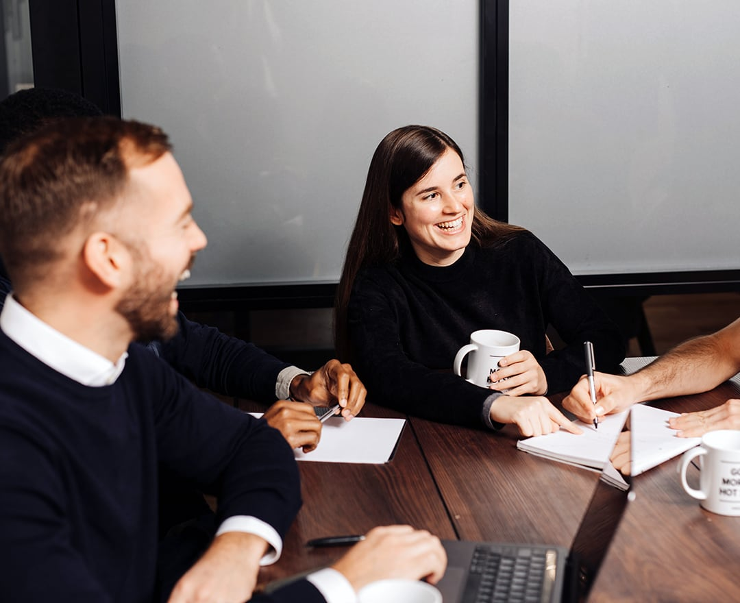 Colleagues laughing in meeting room