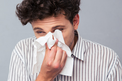 Man suffering from runny nose and allergy symptoms