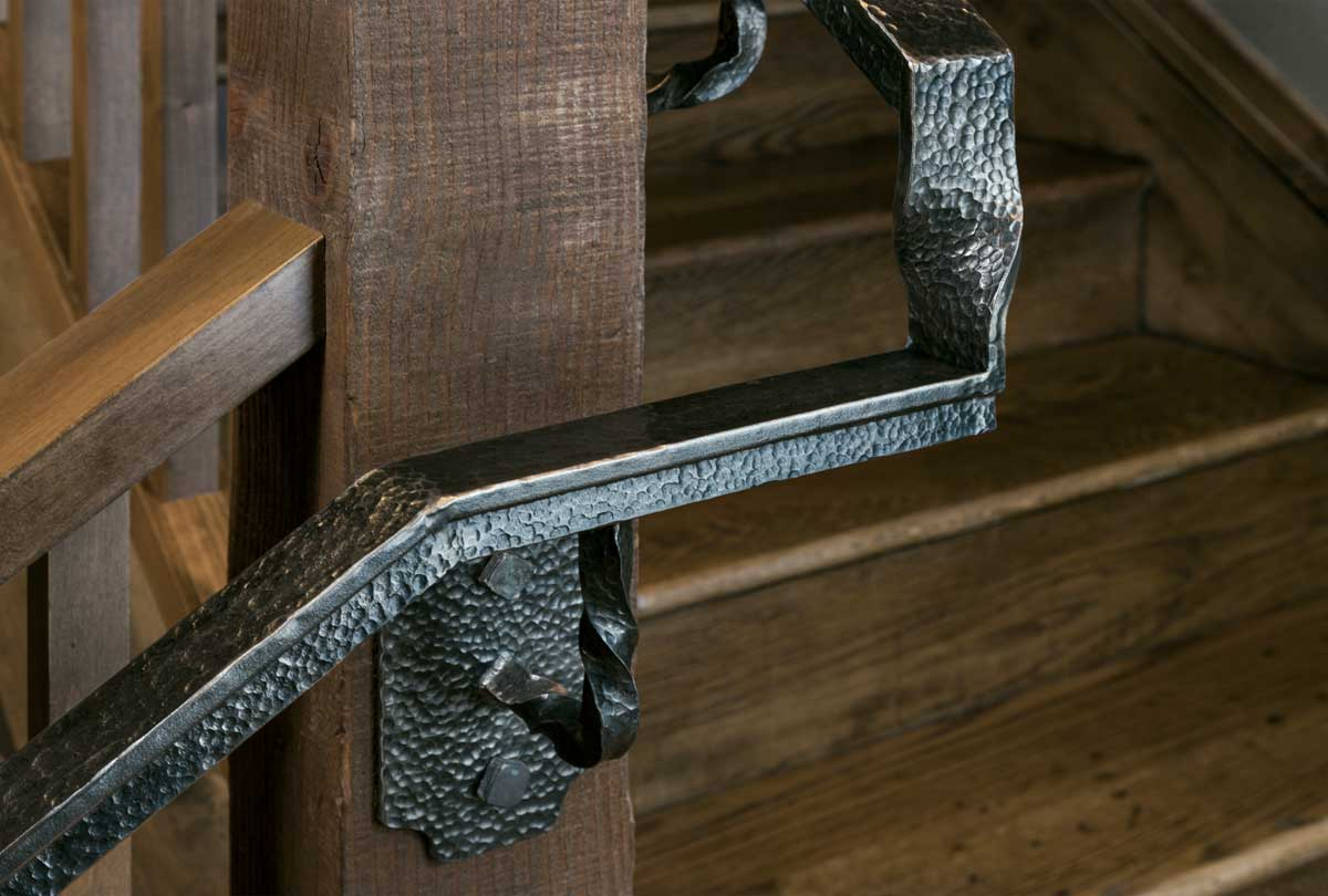 Close up detailed shot of hammered metal railing on wooden staircase