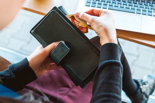 woman pulling credit card out of wallet