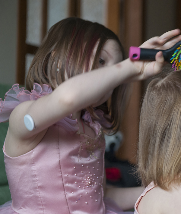 Young girl wearing a remote blood glucose monitor