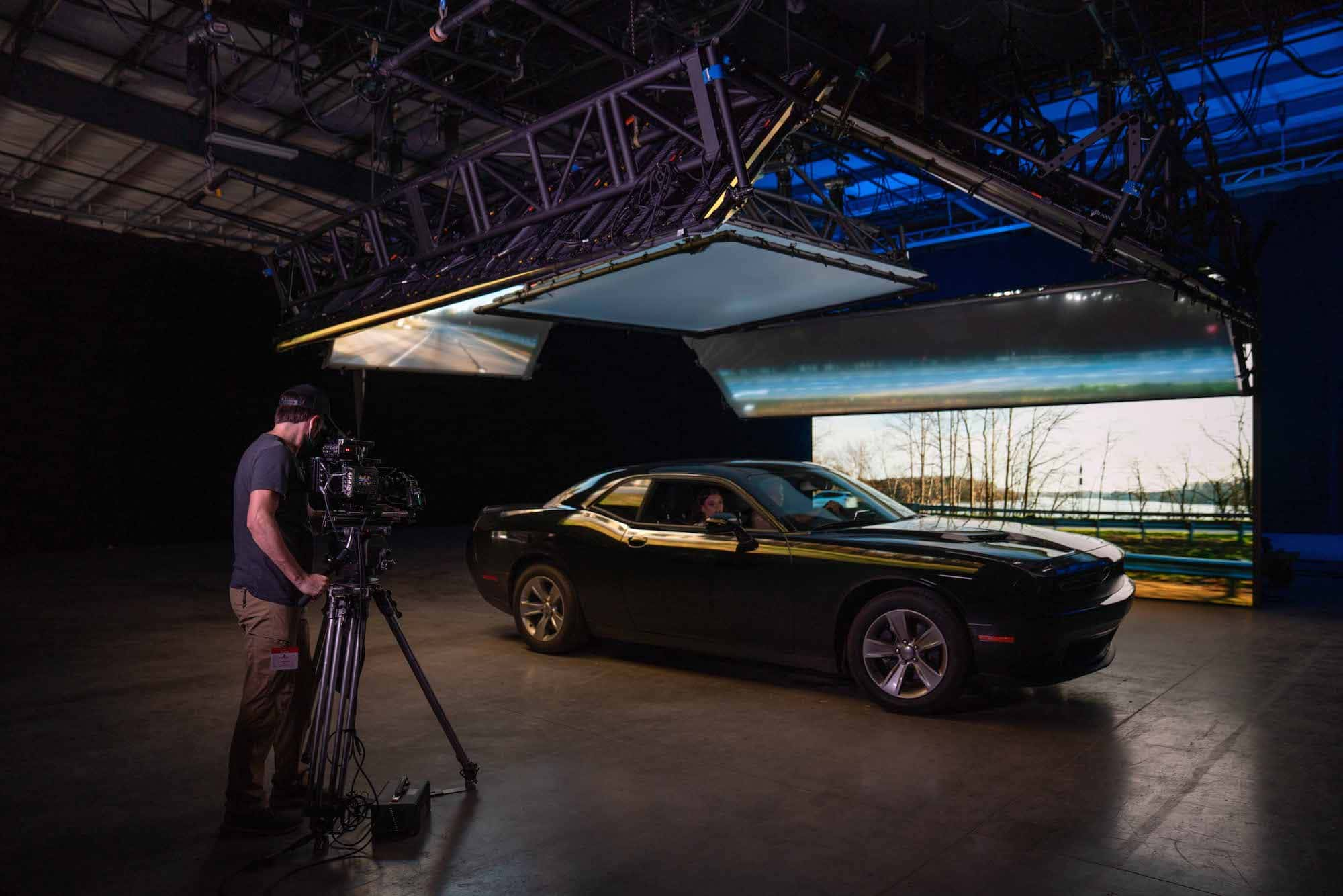 Medium shot of a man filming a car inside of a studio stage. A screen behind the car displays a landscape, mimicking the movement of the car.