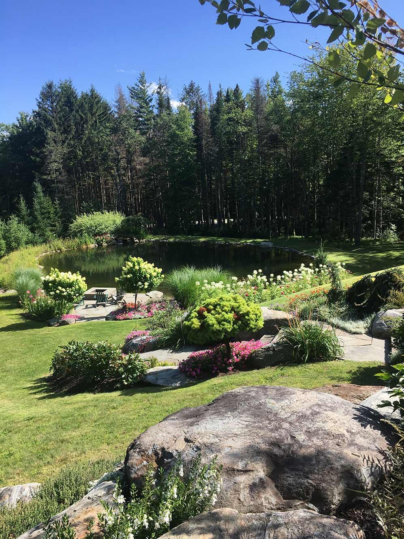 A garden designed by Gardens of Eden overlooking a pond