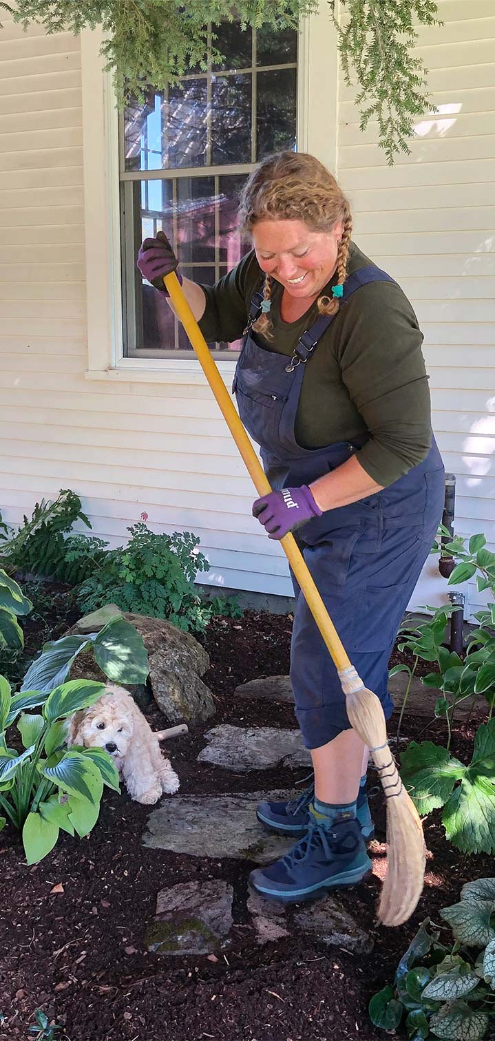 Maggie, the owner of Gardens of Eden is cleaning up a job after mulching garden. beds