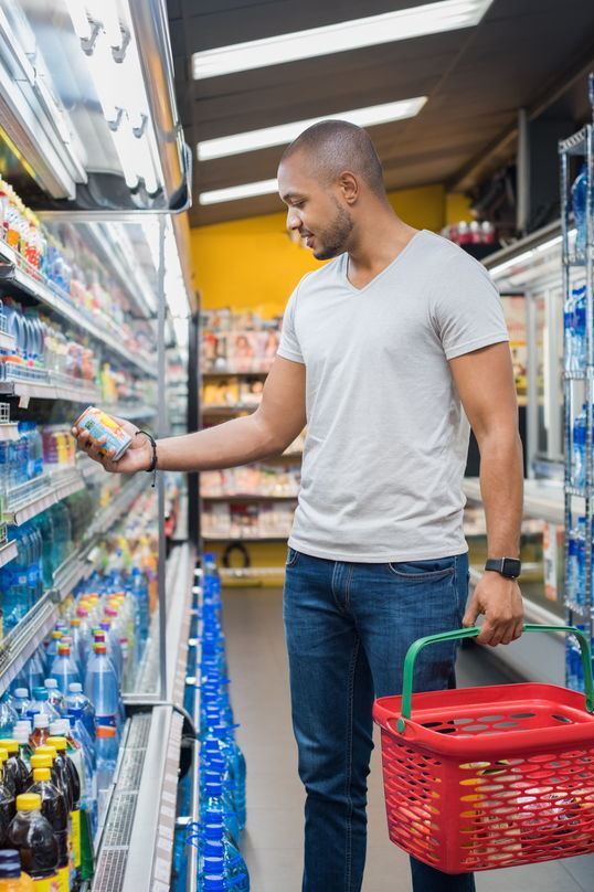 Male shopper with grocery basket looking at item on shelf.