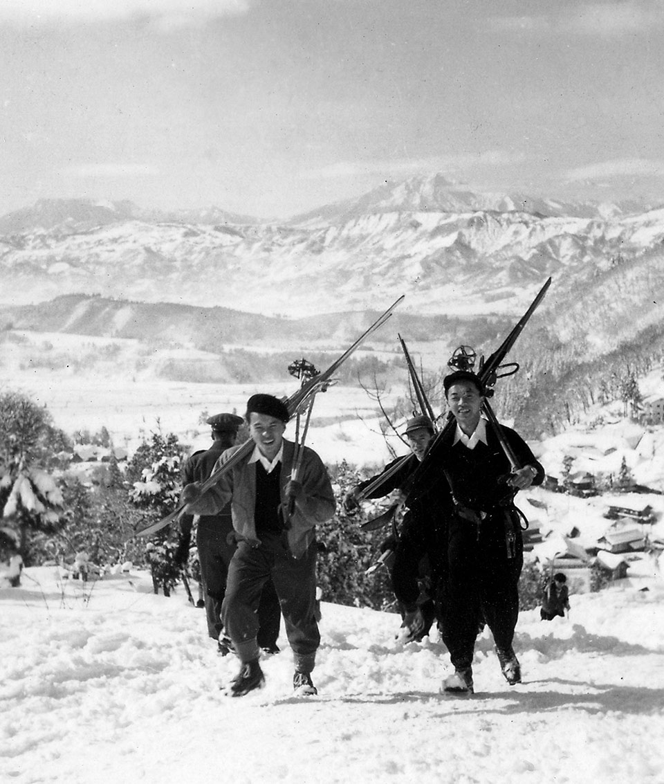 Old picture of two men walking up the mountain while carrying skiing equipment