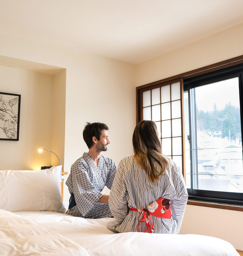 A couple sitting on a bed at the Yasushi Residence