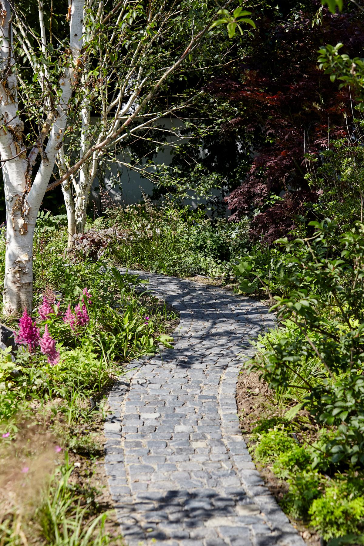 Verwunschener Garten mit Weg aus Naturstein