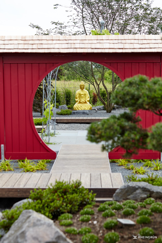 Origineller japanischer Garten mit goldener Buddha-Statue in Kiesbeet