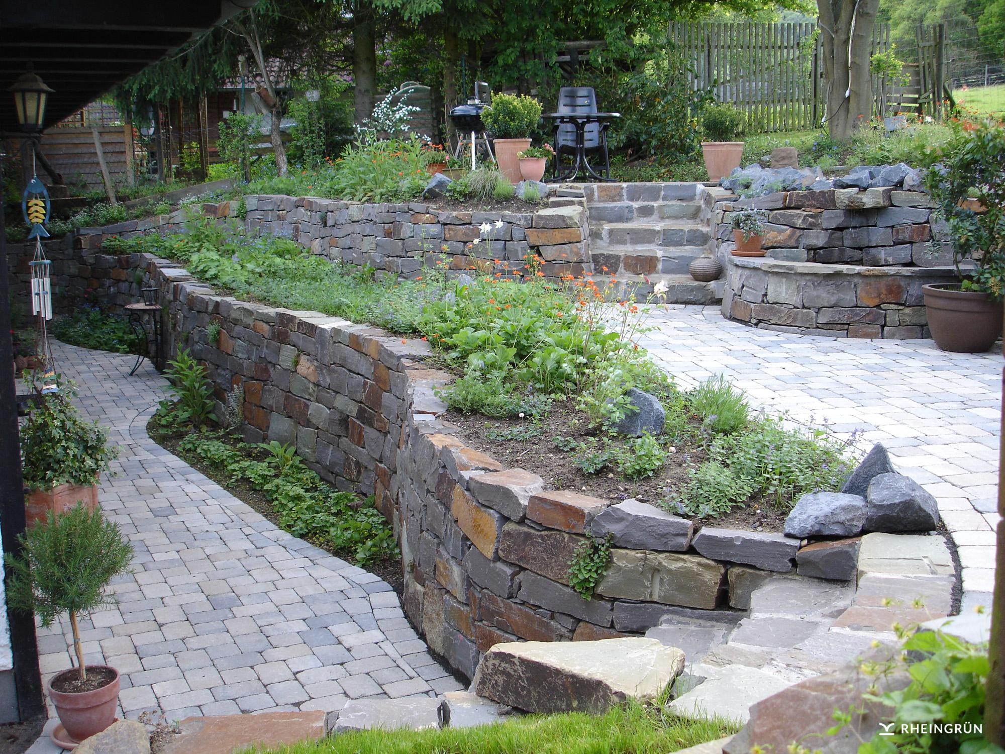 Verwunschener Kräutergarten mit Brunnen und Hochbeet aus Naturstein