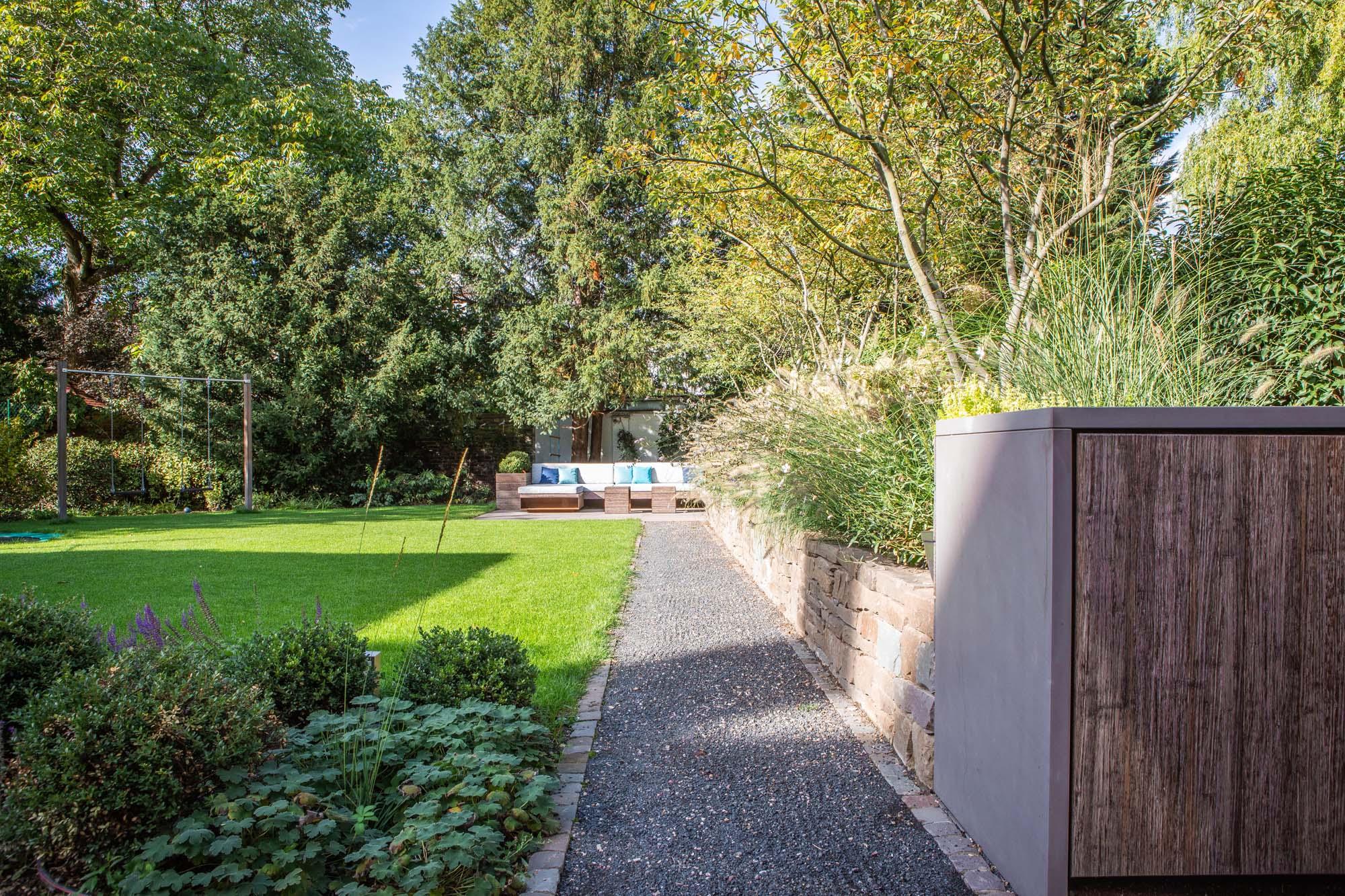 Schöner Familiengarten mit Natursteinmauer und Mediterraner Bepflanzung