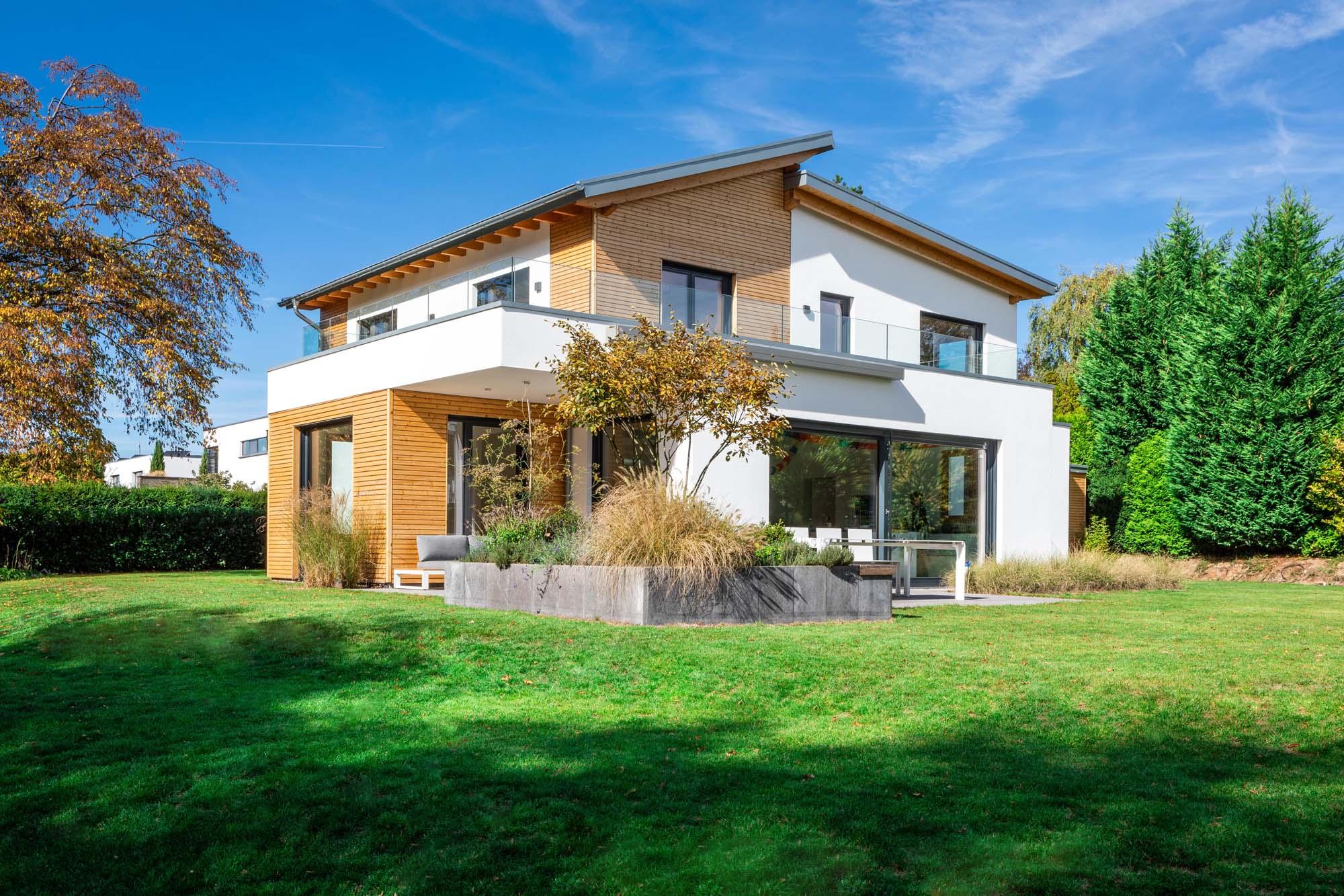 Landvilla mit Holzfassade vor großer Rasenfläche und Obstgarten