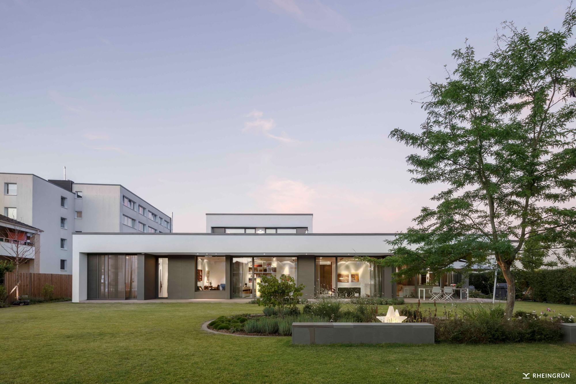 Villa mit Flachdach, großer Rasenfläche und akzentuierter Bepflanzung