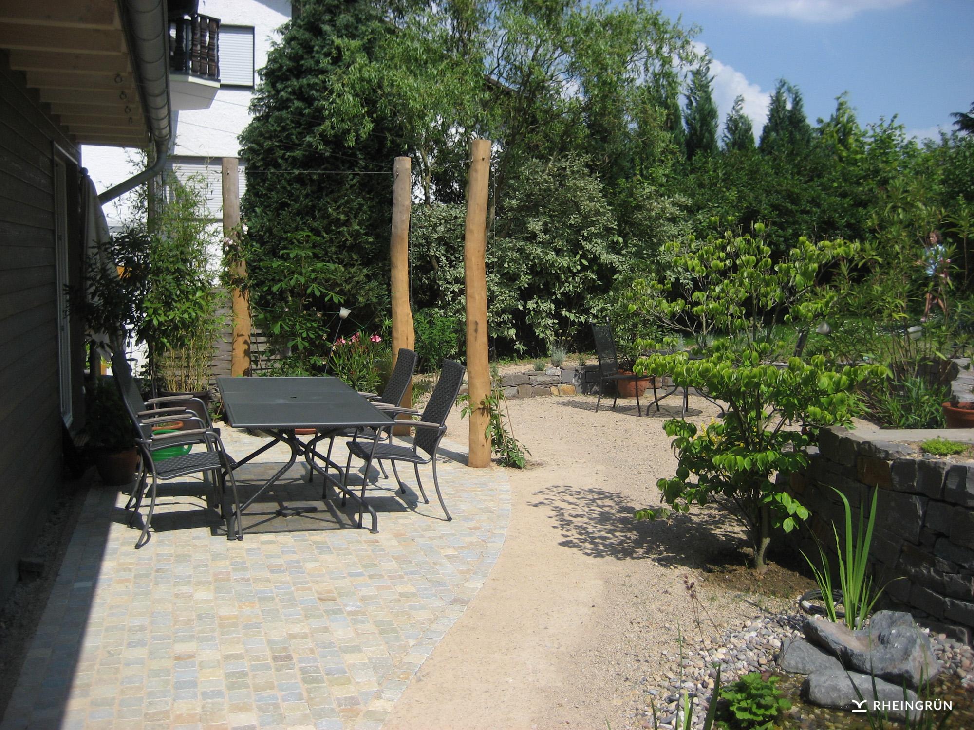 Rustikaler Privatgarten mit Gartenteich und Mauer aus Naturstein