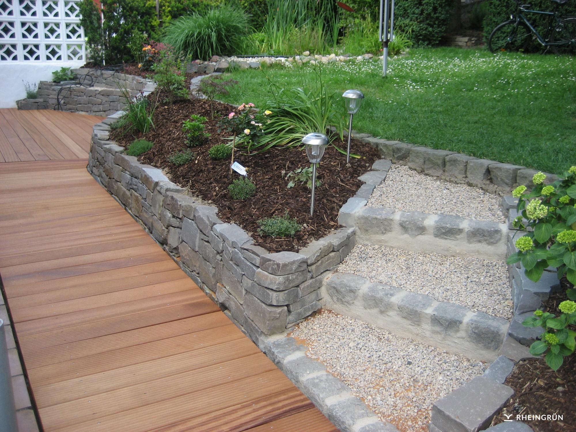 Schöner Privatgarten mit individueller Terrasse aus Holz und Natursteinmauer