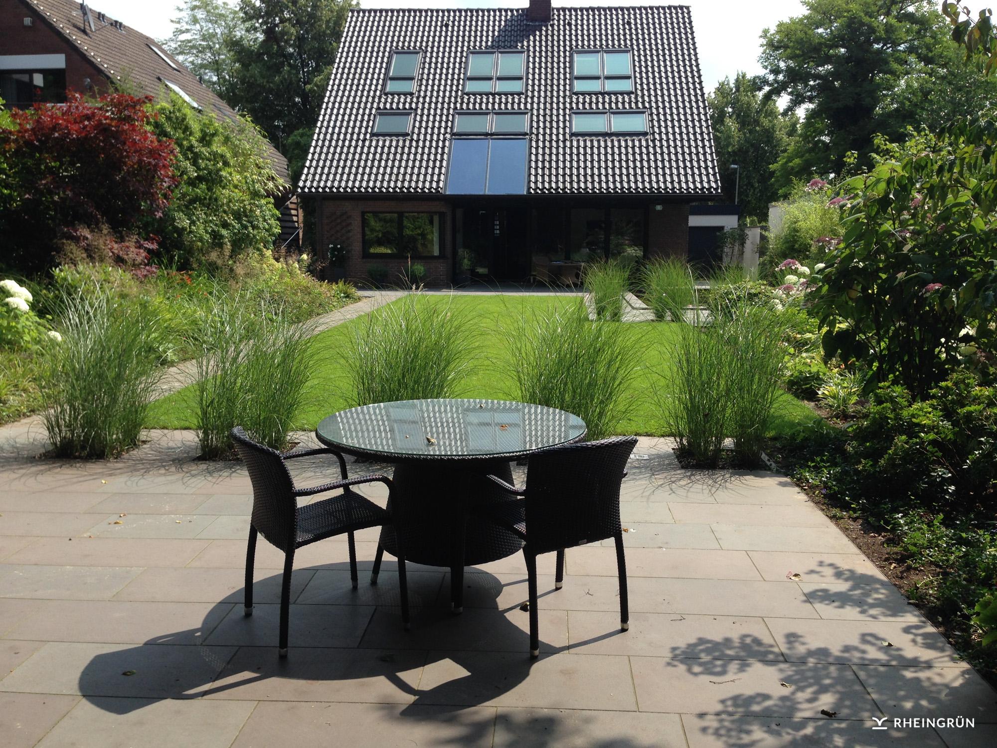 Klassischer Hausgarten mit Teich und großer Terrasse aus Naturstein