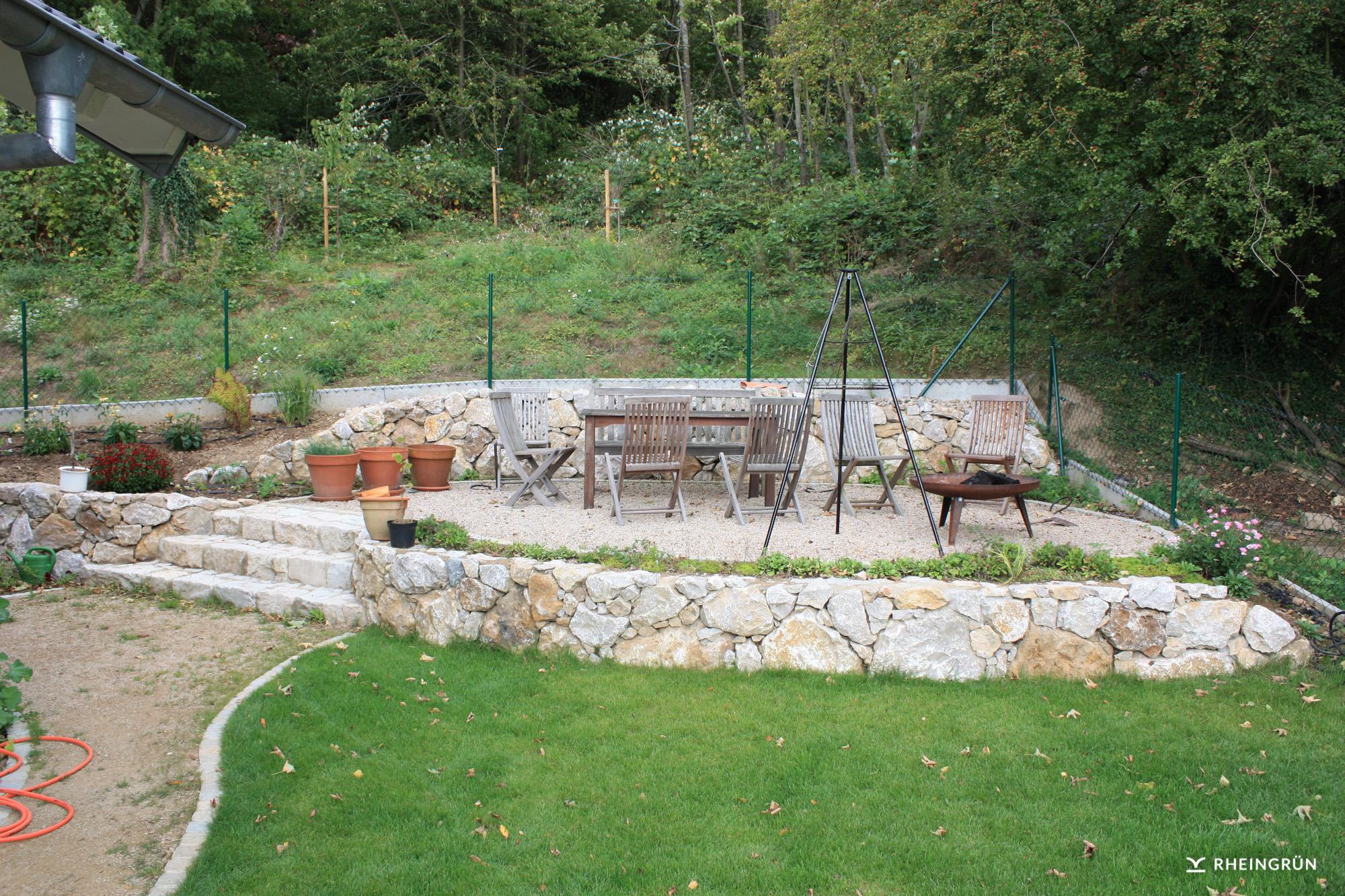 Terrassengärten aus Naturstein mit verschiedenen Kräutern und Treppe aus Naturstein