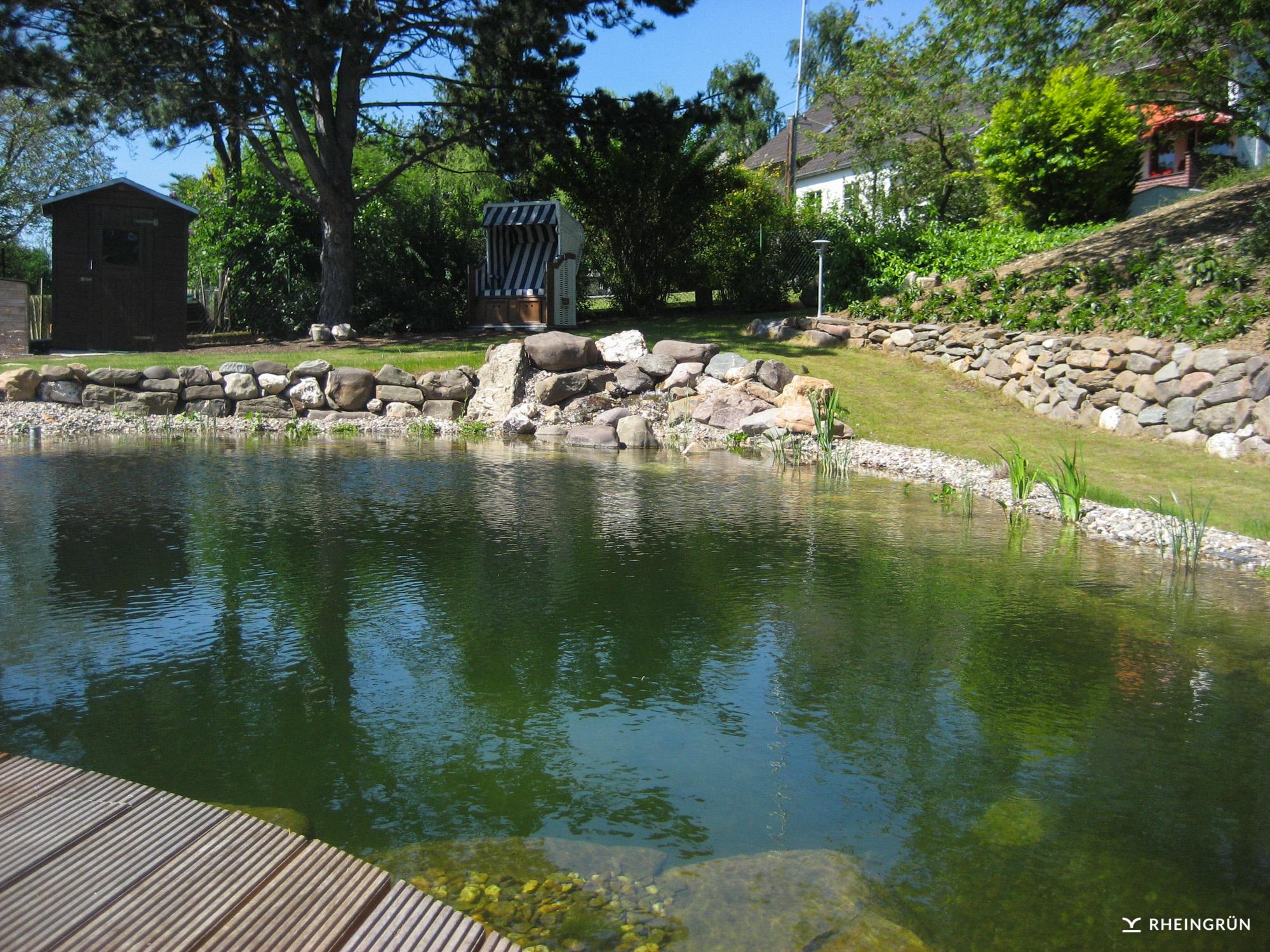 Naturnaher Schwimmteich am Hang mit Strandkorb und Holzterrasse