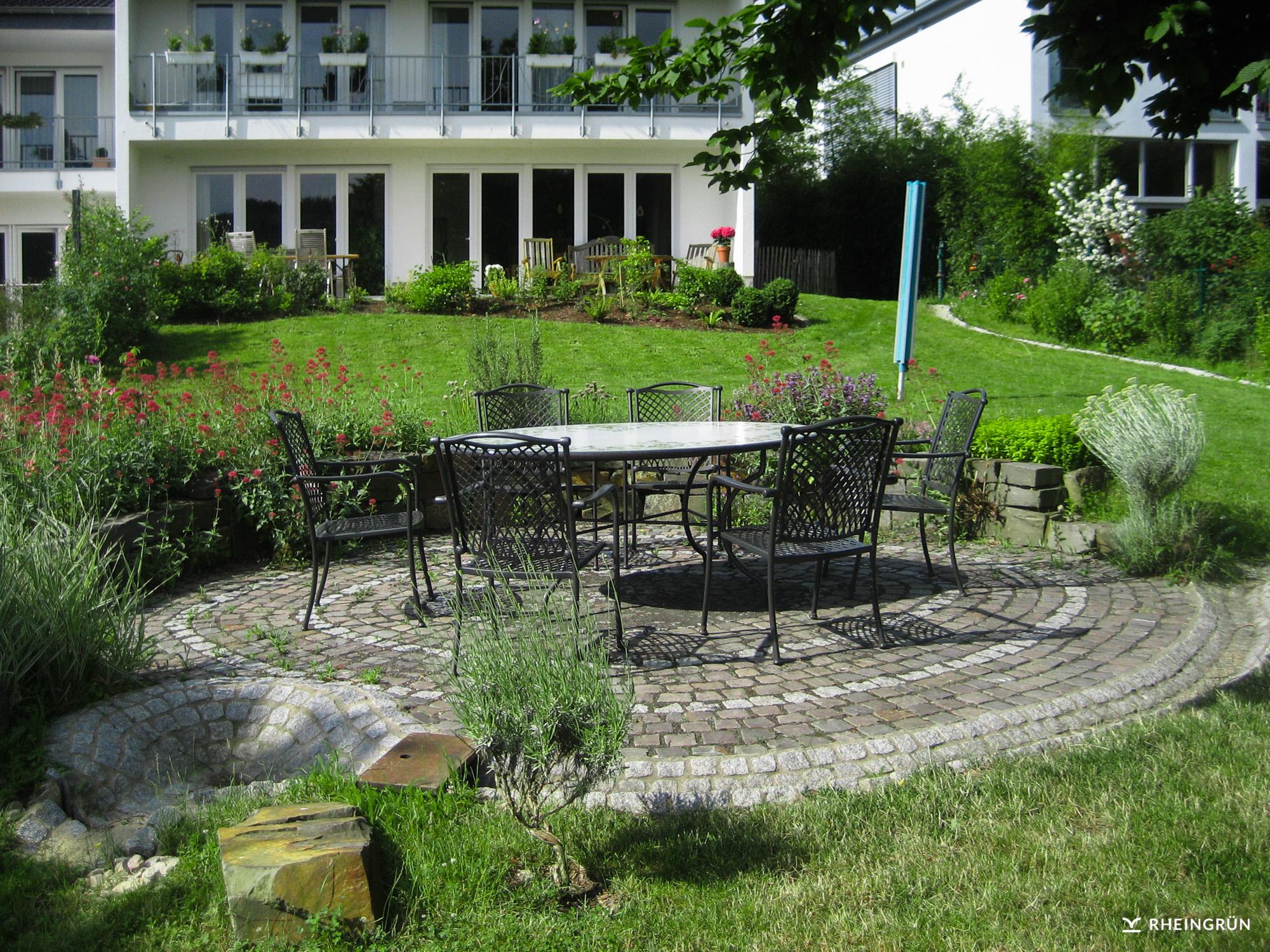 Klassischer Familiengarten mit Terrasse aus Naturstein und Spielwiese