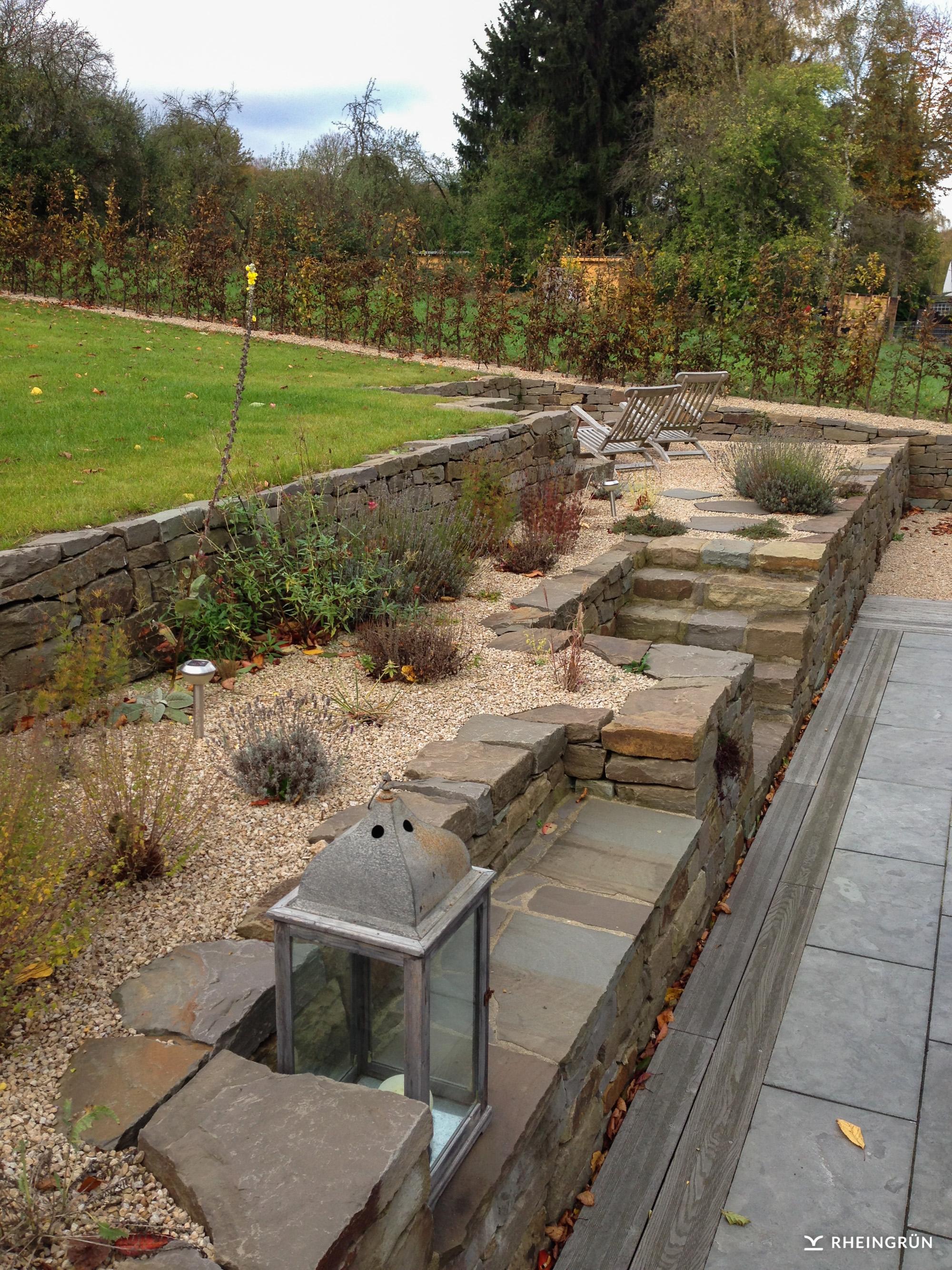 Rustikaler Privatgarten mit Terrasse und Mauer aus Grauwacke