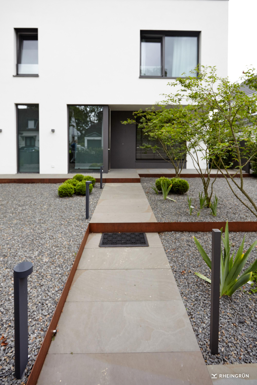 Geradlinige Gartengestaltung mit großen Platten aus Naturstein und Elementen aus Cortenstahl
