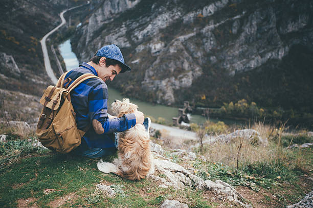 Young brunette man hiked atop a small cliff with his pet dog sitting next to him looking up
