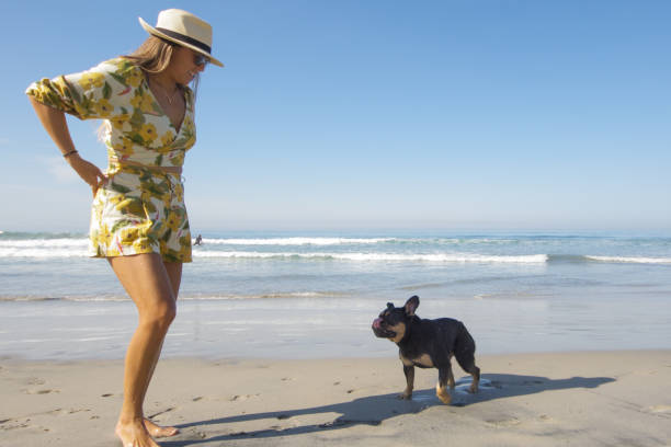 Brunette woman wearing floral bathing suit and sun hat on the beach with her grey and brown French Bulldog off leash