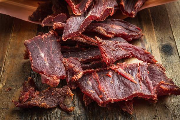 Beef jerky cut in slices spread on wooden board