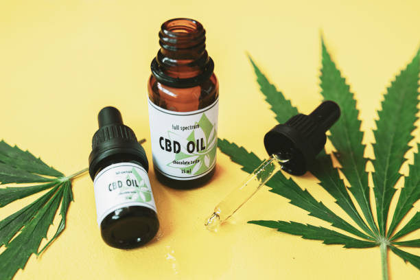 CBD oil, Cannabis oil on yellow background. CBD oil and cannabis leaf on yellow background. cbd stock pictures, royalty-free photos & images