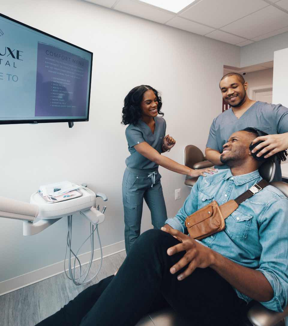 Photo of Washington DC dentist Dr. Ashley Fagan and a team member with a patient in a dental chair
