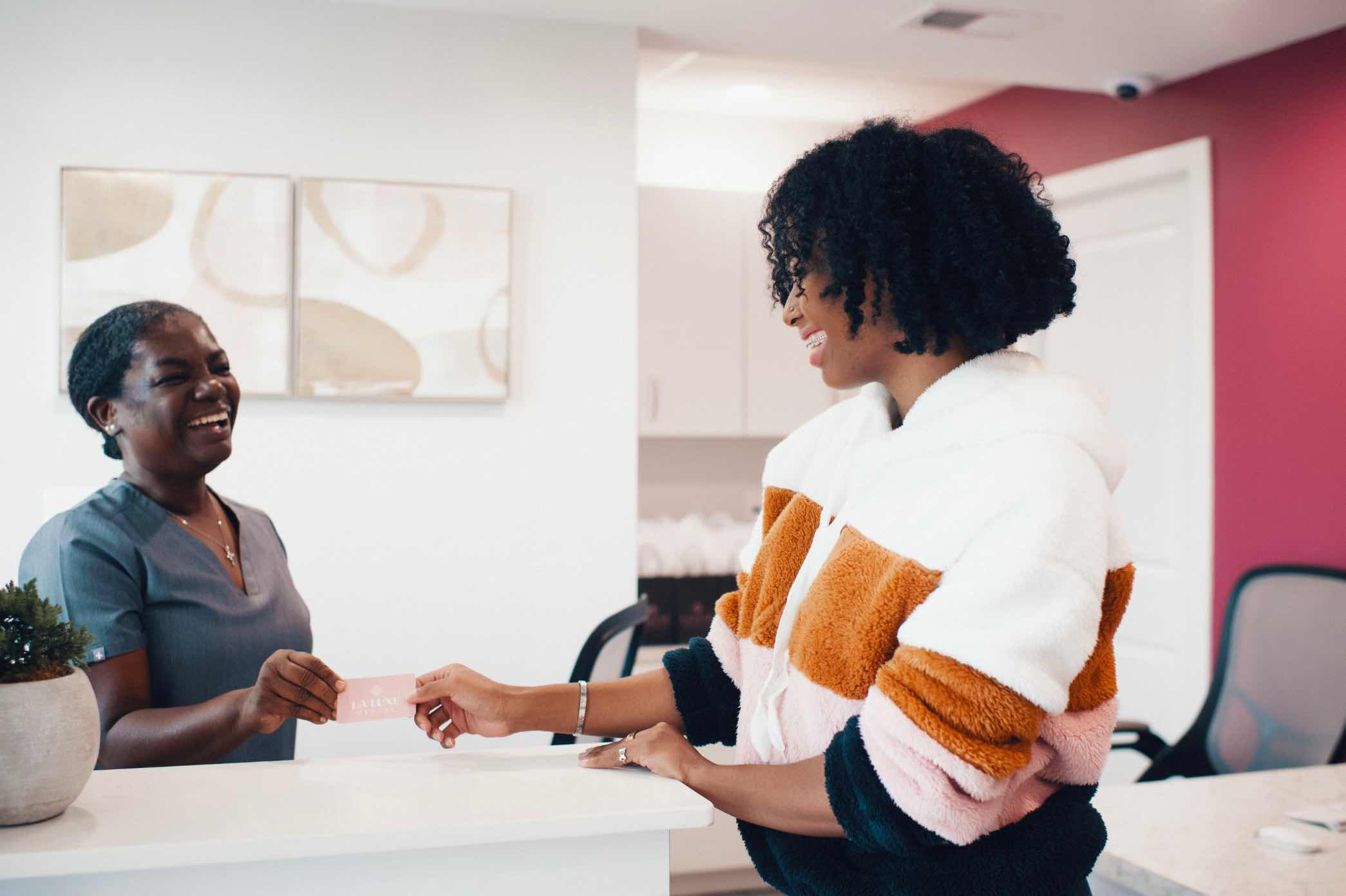 Photo of a team member with a patient at the front desk