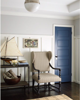 New England-style foyer decor with chair, sailboat, and blue door