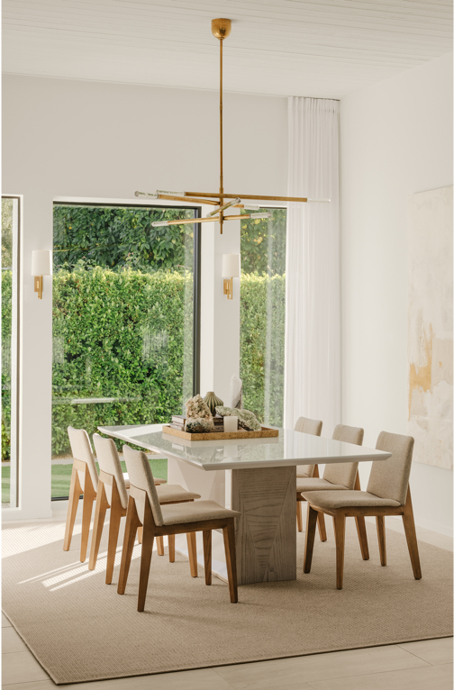 Modern dining table with chairs, high ceilings, and window looking out on greenery