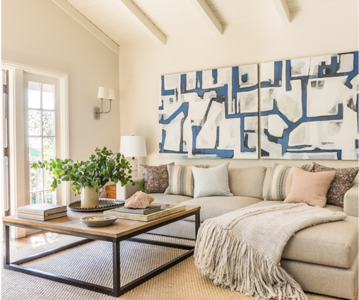 Living room with white walls, couch, coffee table, and large art piece