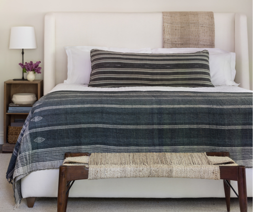 Bed with blue striped bedding and matching pillow