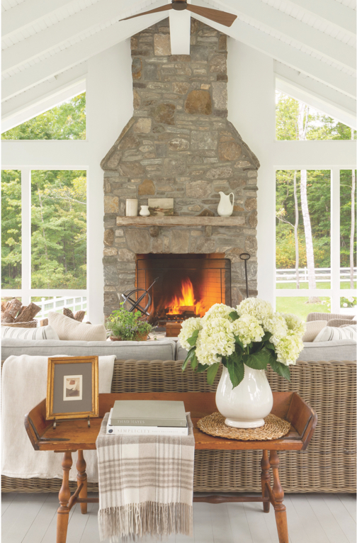 Living room with large stone fireplace, vaulted ceilings, sofa table, and large windows