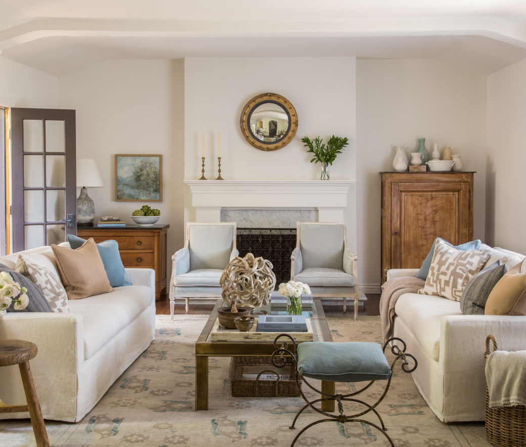 Symmetrical living room with two couches, two chairs, armoires, and a fireplace