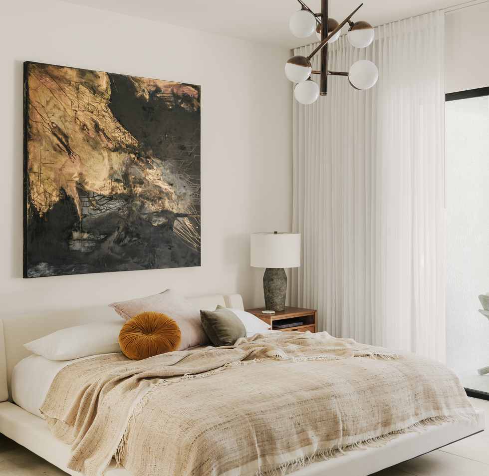 Bedroom with tan bedding, accent pillows, large gold and black art piece, and interesting light fixture
