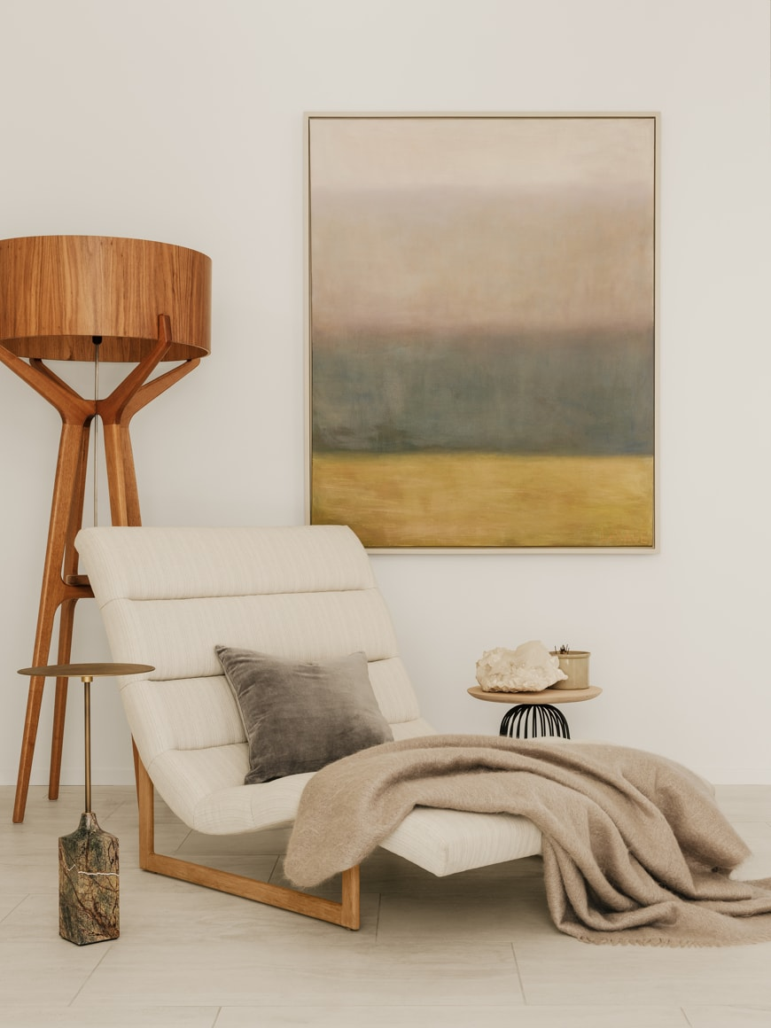 Large accent chair with throw blanket, wooden floor lamp, and modern art piece on wall