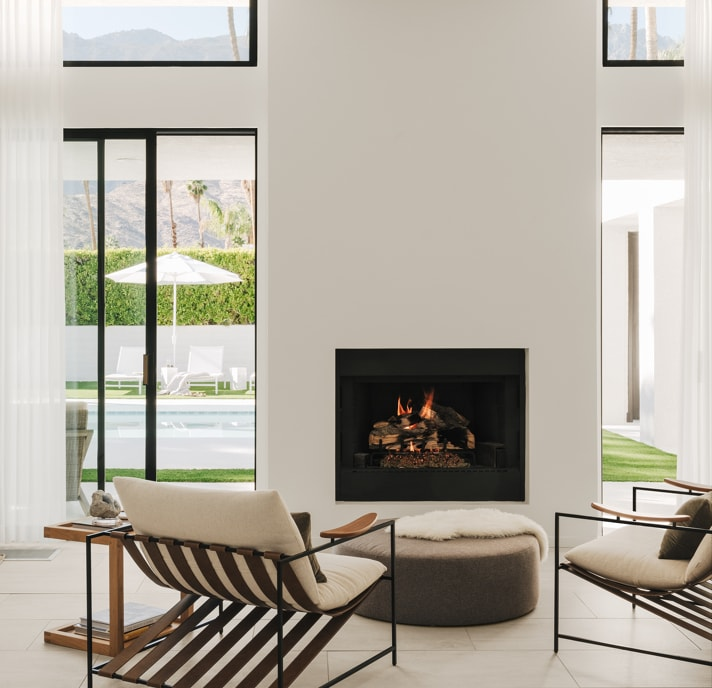 Living room with modern ergonomic chairs in front of a fireplace and large windows looking out to pool area